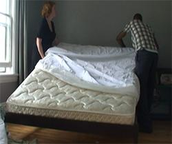 two people putting an encasement on a mattress to prevent bed bugs